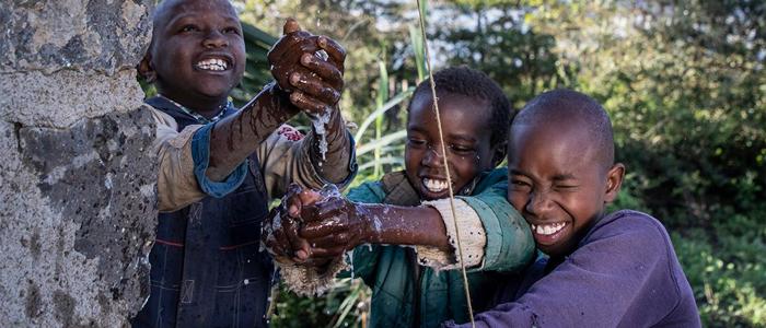 three boys washing hands