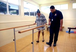 Inside a clinic room, a woman uses parallel bars to support herself while she practises walking with her new lower limb prosthesis. A man in a service uniform is walking alongside her, matching her steps and watching closely to make sure she is safe. Image courtesy of Motivation Australia