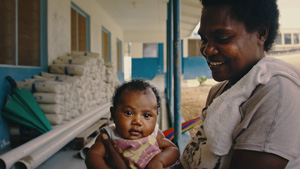 melanesian woman mother with her child at waiting at the local village health center hospital