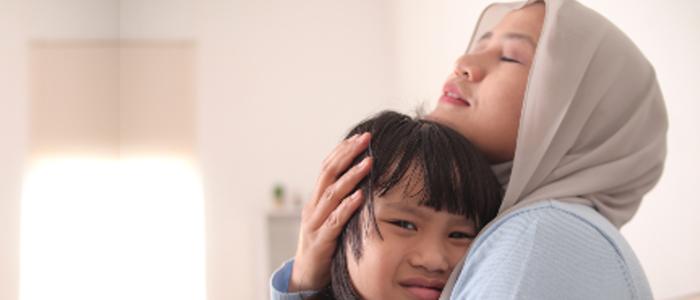 Indonesian woman holding sad child