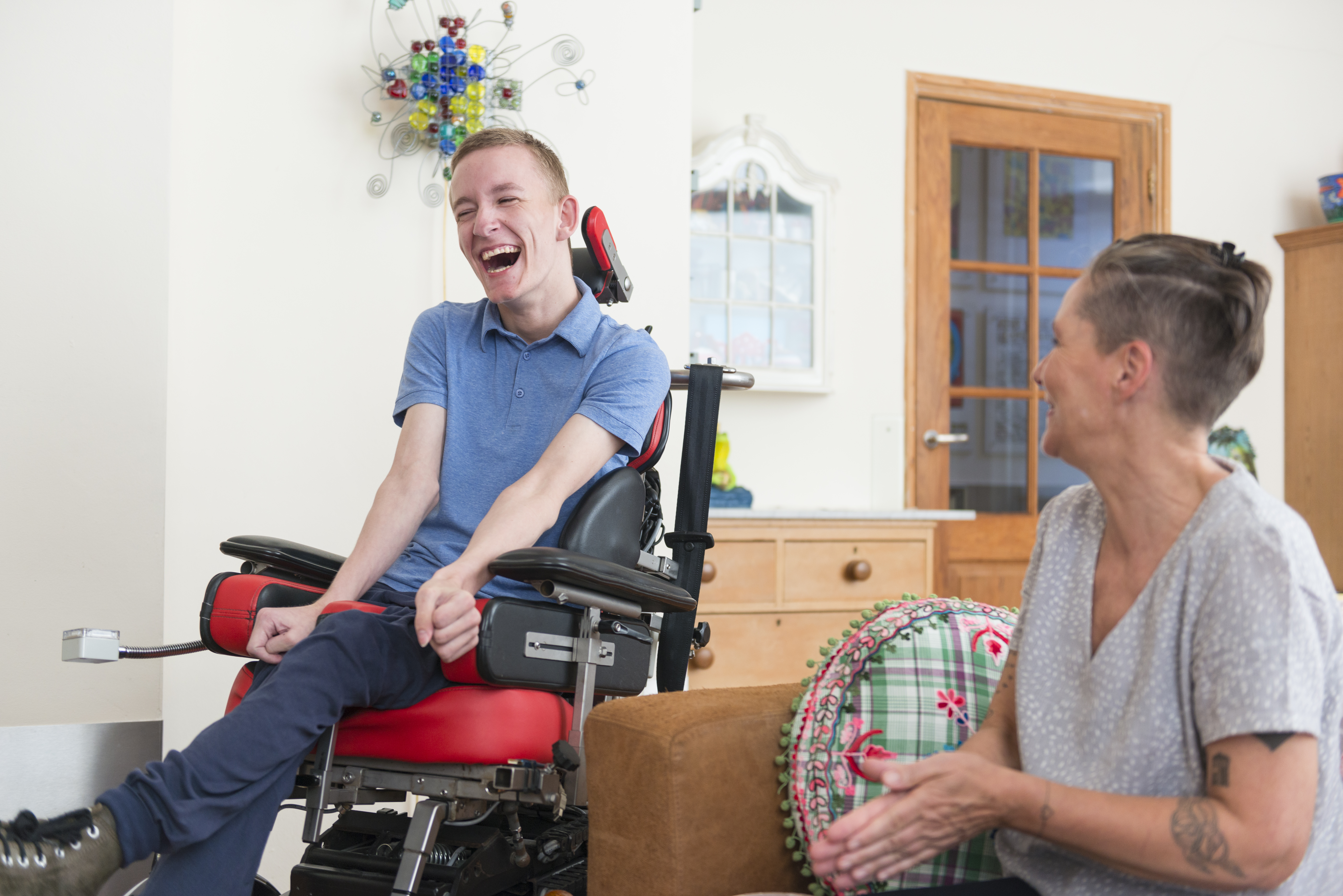 Young man seated in wheelchair having a laugh with his carer