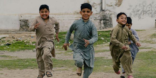 Three young laughing Pakistani boys running toward the camera