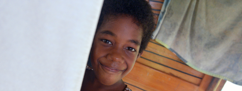 Young Fijian girl smiling  partially hiden behind a white wall