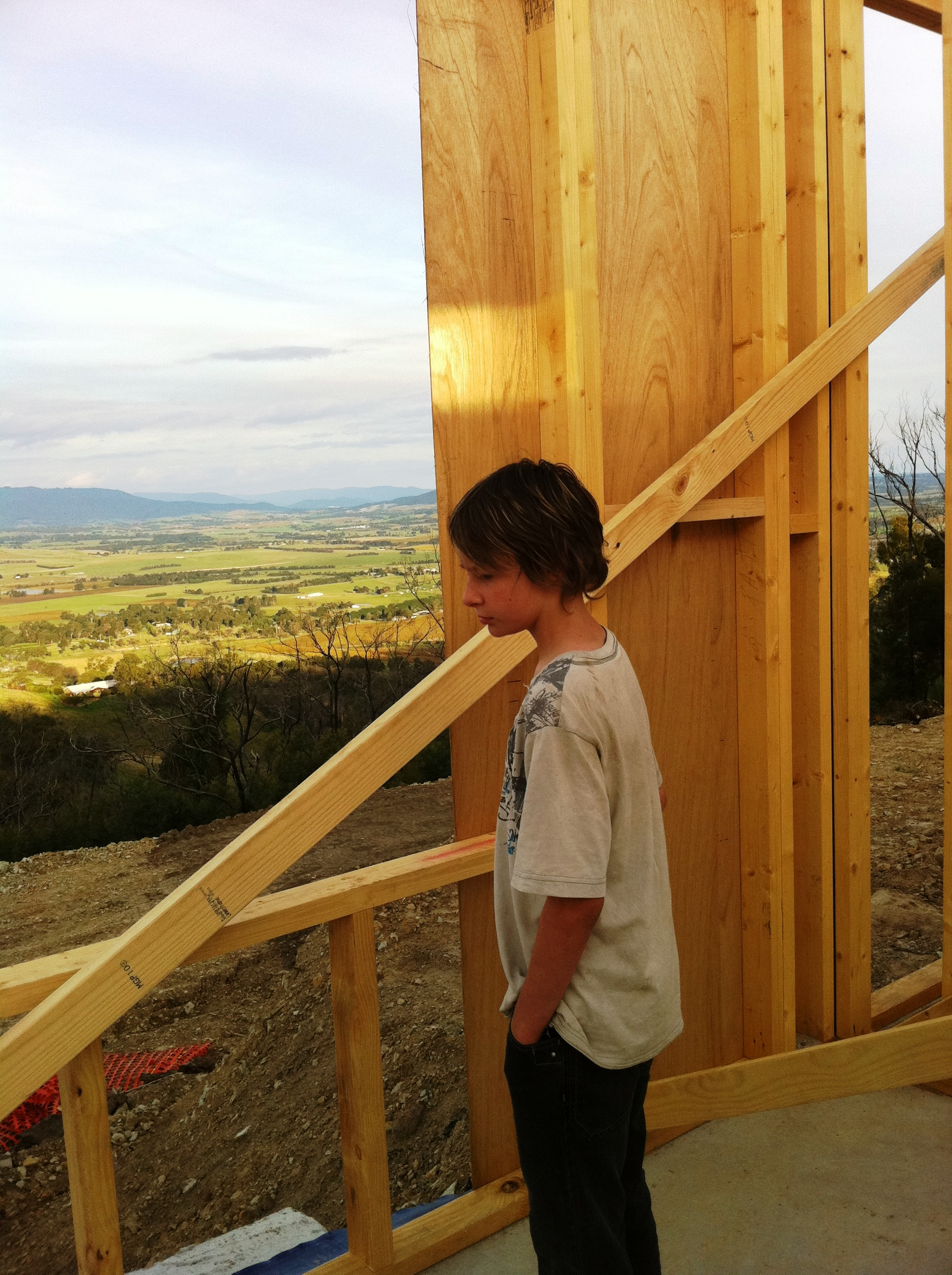 Child looking out from house scaffolding over fields