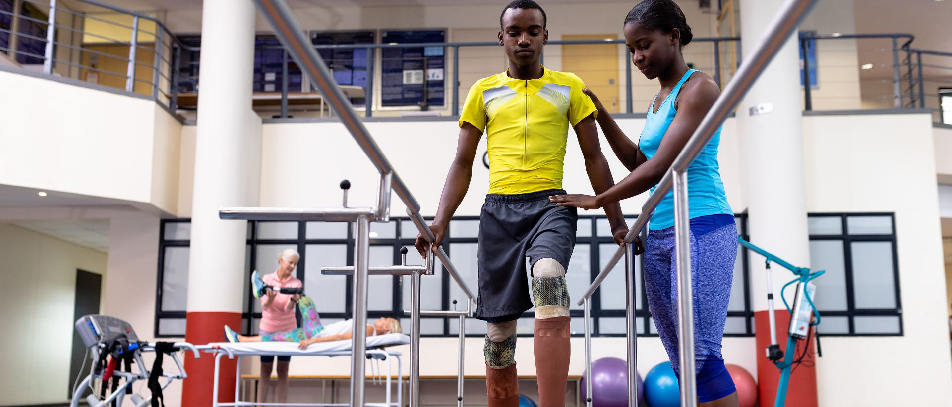 Low angle view of African-american physiotherapist helping disabled African-american man walk with parallel