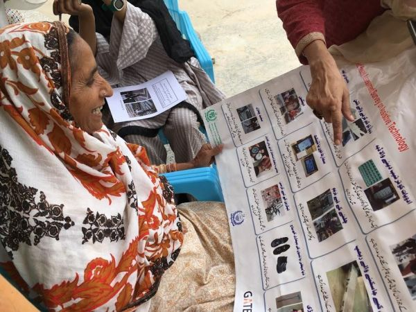 CREDIT @WHOPakistan Elderly women holding a large piece of paper with picture of differenet types of Assistive Technology